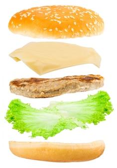 Вкусный гамбургер с летающими ингредиентами на белом фоне