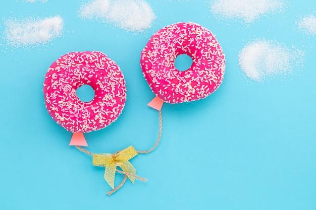 青色の背景にドーナツ、空に風船の形をしたドーナツ