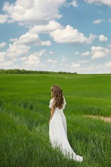 日当たりの良い夏の日の屋外のロマンチックな美しい花嫁。美しいウェディングドレスの若いブロンドの女性がフィールドを走っています。
