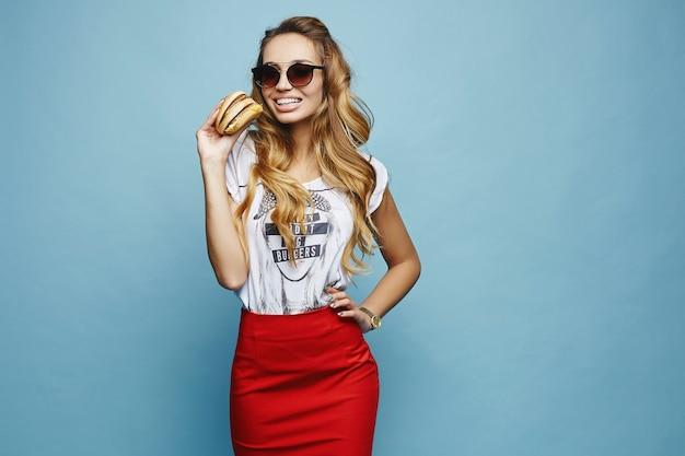 Модельная девушка в красной юбке и футболке держит двойной бургер и улыбается,