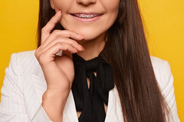 Обрезанный портрет улыбающегося привлекательной молодой женщины в брекеты