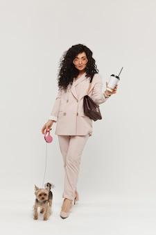 Модельная женщина в модном наряде держит кофейную чашку на вынос и гуляет с маленьким йоркским терьером