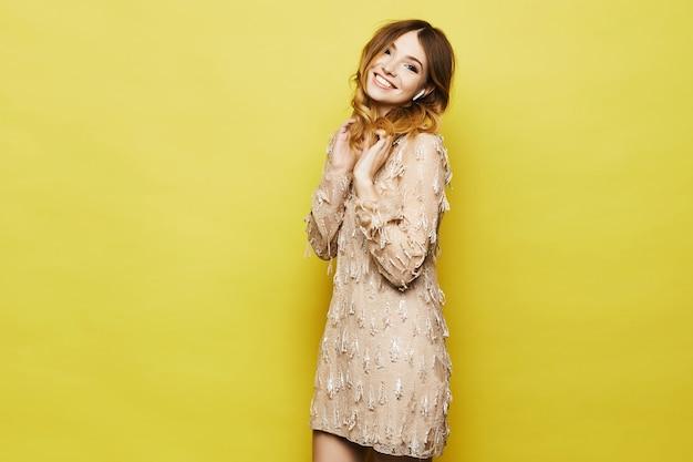 Модная и эмоциональная светловолосая модель с ярким макияжем и блестящей улыбкой, в стильном персиковом платье позирует