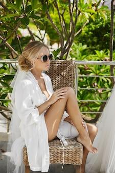 Красивая и модная блондинка, модельная женщина с сексуальным телом в белом пеньюаре и нижнем белье, в стильных солнечных очках сидит на стуле, наслаждаясь солнцем и позируя на улице