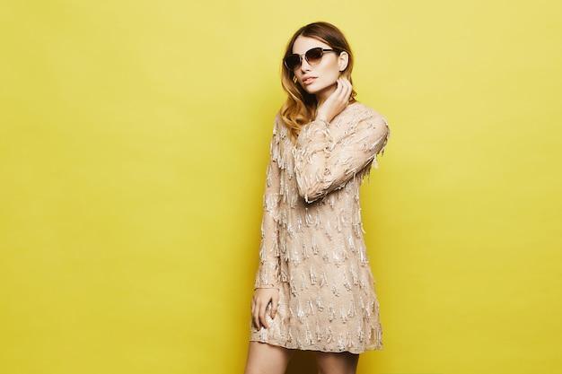 Модная и обаятельная белокурая модель с ярким макияжем в стильном персиковом платье и модных солнцезащитных очках поправляет прическу и позирует