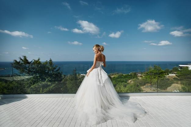 立っていると海を見てウェディングドレスの美しい若いブロンドモデルの女性