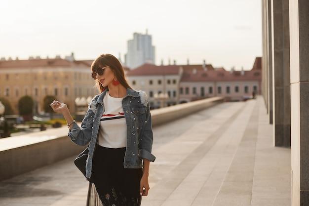 Молодая женщина в модной летней одежде гуляет по улице города в летний день.