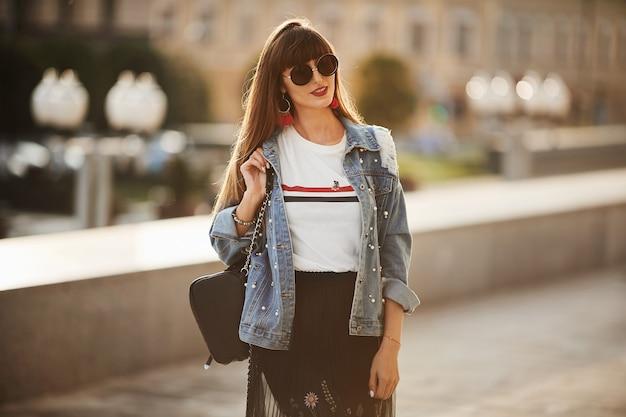 Молодая модель в джинсовой куртке и круглых очках позирует на солнечной улице в летний день