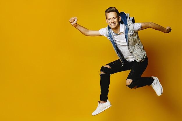 分離された黄色の壁でジャンプデニムの服で幸せな若い流行に敏感な男の側面図です。