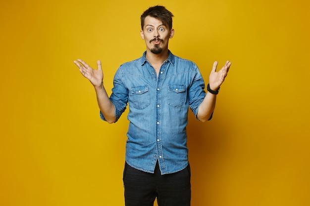 Удивленный молодой человек, стильный хипстер с бородой и усами в модной джинсовой рубашке