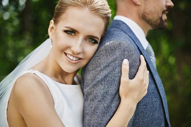Элегантная и модная невеста обнимает своего красавца в костюме