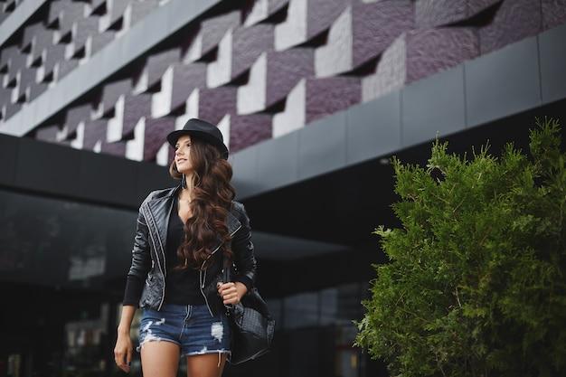 モダンな建物の近くの通りに、革のジャケット、黒い帽子、ジーンズのショートパンツでスタイリッシュなバックパックとウェーブのかかった髪のモダンなモデルの女の子が立っています。トレンディなカジュアルな服装。毎日見て。ストリートファッション。