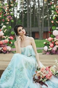 エキゾチックな花のブライダルブーケを押しながら花の背景でポーズのウェディングドレスのブルネットのモデルの女の子