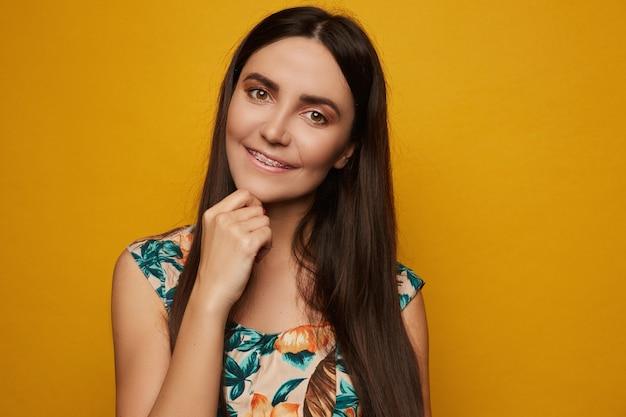 中かっこを持つ若いラテン系モデルの女の子は笑みを浮かべて、分離された黄色のポーズ