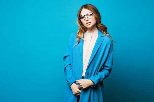 ナチュラルメイクとトレンディな青いコートを持つ美しい若い女性