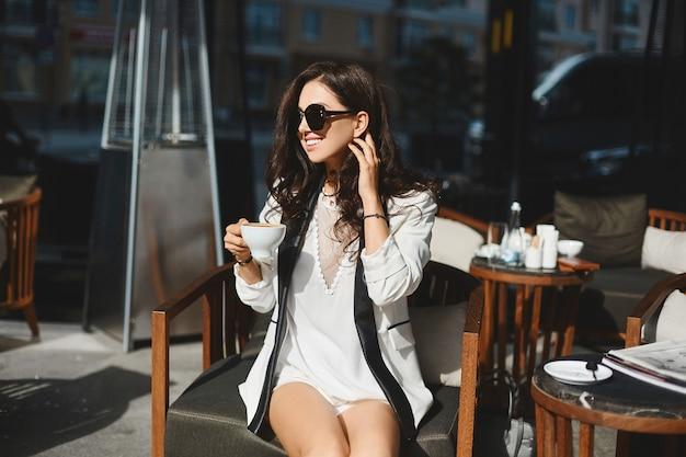 白いスーツの若い実業家が夏の日のカフェでコーヒーブレーク