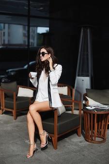 夏の晴れた日にカフェでポーズをとっておしゃれな服で完璧なボディを持つ若い女性
