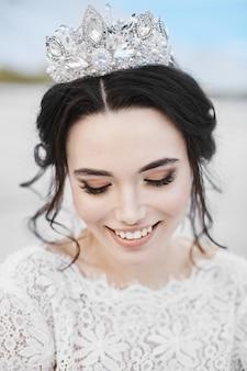 Модельная девушка с модной диадемой на голове улыбается и позирует с закрытыми глазами