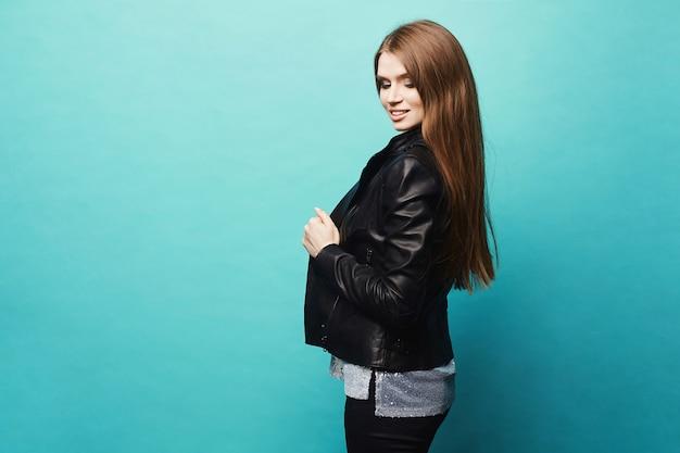 スタジオで水色の上ポーズレザージャケットの長い髪の美しく、セクシーなモデルの女の子。トレンディな衣装で明るいメイクと若いきれいな女性の側面図。トリミングされた肖像画