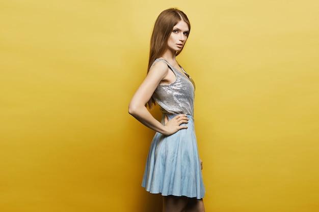 青いスカートと黄色でポーズをとって銀のブラウスでスリムな姿のモデルの女の子。テキスト用のスペースをコピーします。