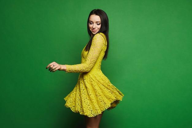 Брюнетка-модель с ярким макияжем в коротком стильном желтом платье кружится