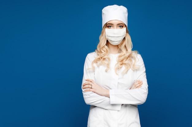 分離された青に白い医療ガウンの若い女性。医療制服とフェイスマスクの女医。一般開業医または看護師が白い制服を着てポーズします。