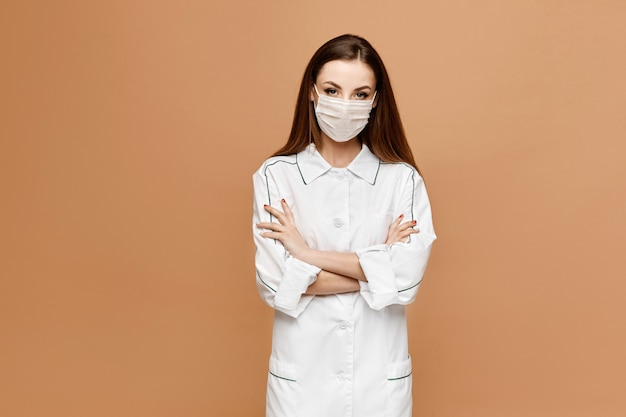 Женский доктор с защитной маской позирует. молодая женщина в медицинской форме и защитной медицинской маске