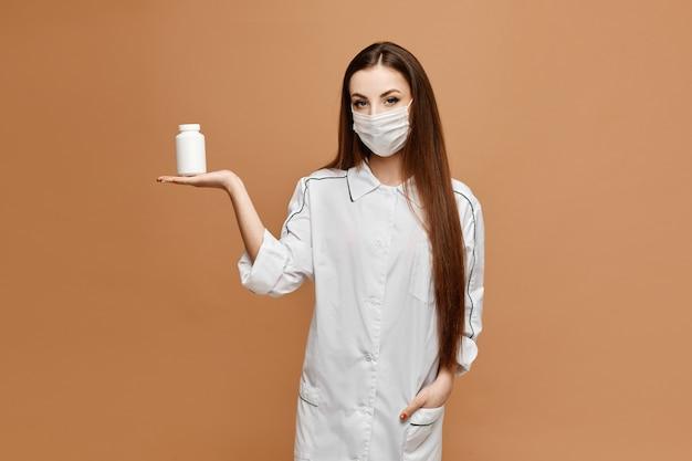 医療服と薬の瓶で保護マスクでポーズの若い女性。女医は、錠剤を手に保持します。ウイルスとインフルエンザの保護薬の概念。