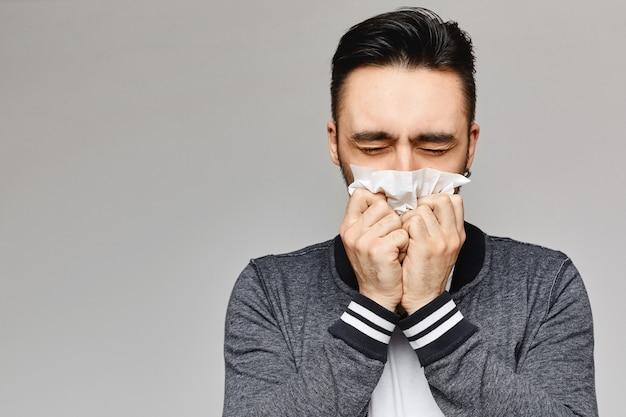若い男のくしゃみと紙ナプキンで口を覆っています。