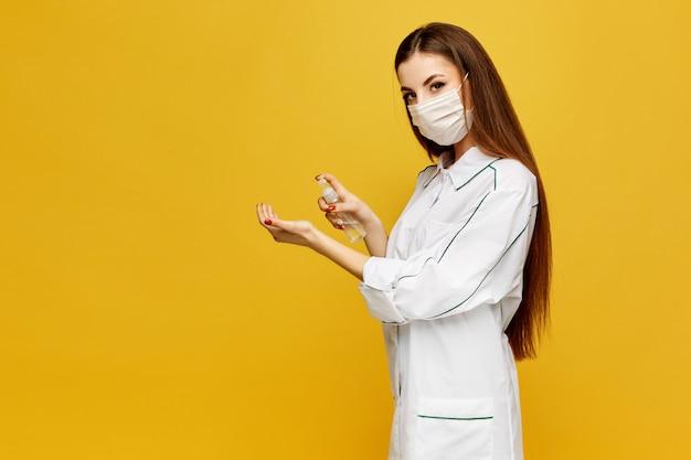 Молодая женщина-врач в белом халате и защитной маске надевает на руки дезинфицирующее средство. молодая женщина в медицинской форме кладет антисептик на руки. концепция гигиены.
