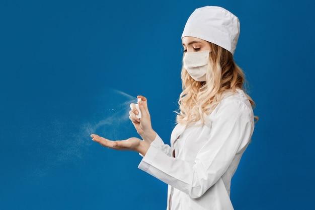 消毒剤アルコールスプレーを保持している外科用フェイスマスクを着ている女性医師