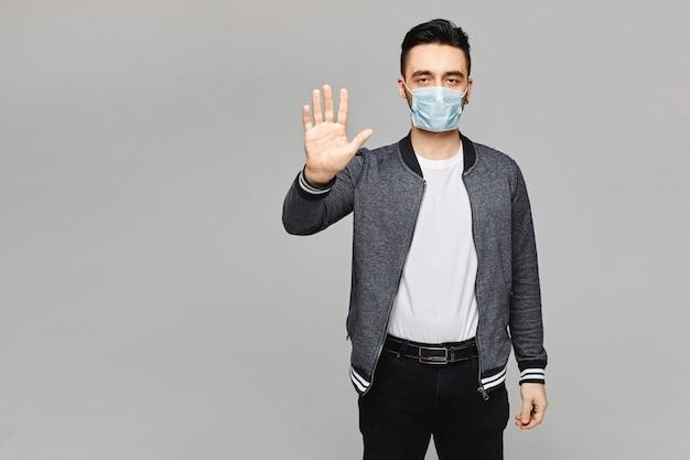 グレーに分離された彼の手でストップモーションを作る防護マスクの若いハンサムな男