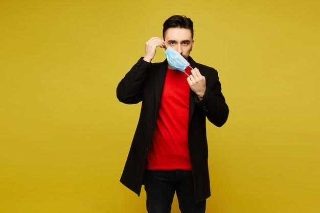 Молодой человек в черном пальто, надевая медицинскую защитную маску, изолированные на желтом фоне с копией пространства для вашего текста. концепция здравоохранения.