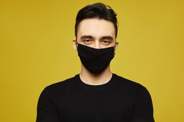 Красивый человек в черной футболке и черной защитной маске, изолированных на желтом фоне. сезонная болезнь и концепция сезонного гриппа. концепция здорового образа жизни
