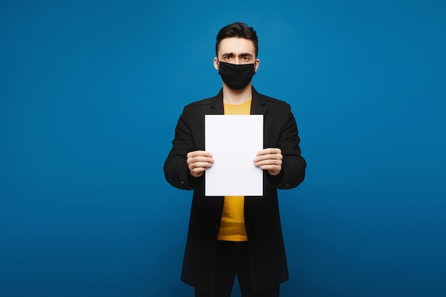 Молодой человек в черном пальто и черной защитной маске представляя с пустым листом бумаги на голубой предпосылке, концепции продвижения. концепция здравоохранения