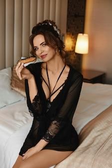 黒のランジェリーと彼女の手でチョコレートケーキを押しながらベッドに座っているスタイリッシュな髪型のセクシーなモデルの女の子。美容、ファッションのコンセプト