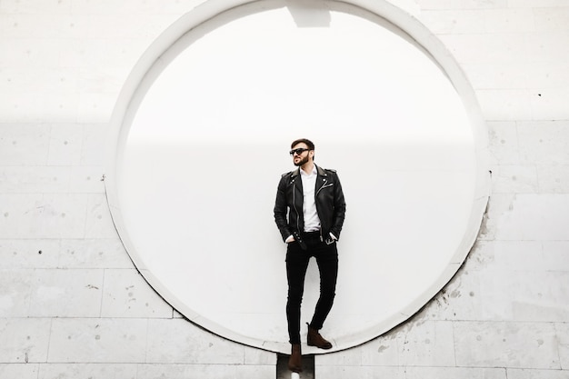 Красивый молодой брутальный мужчина, стильный и модный мужчина с бородой, в кожаной куртке, черных джинсах и черных солнечных очках, позирует на солнечной улице перед белой стеной здания