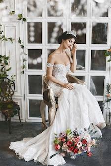 彼女の頭の上の王冠とウェディングドレスの若いブルネットの女性は花の花束と椅子に座っています。