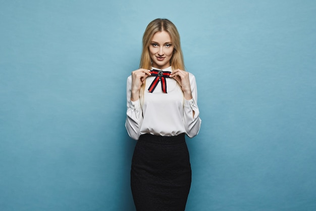 彼女のスタイリッシュなブラウスに弓を調整し、スタジオで青色の背景にポーズをとって黒いスカートで美しく、ファッショナブルな笑顔金髪モデルの女の子