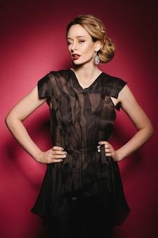 Модная и сексуальная модель-блондинка с ярким макияжем и большими серьгами, в элегантной черной блузке и в черных брюках, подмигивает и позирует на розовом фоне в студии