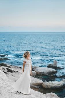 Молодая модельная женщина с идеальным телом в стильном длинном белом платье позирует на скалах на берегу моря на кипре