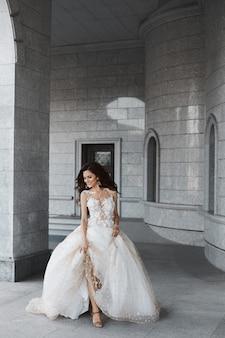 Счастливая молодая невеста со свадебной прической в белом кружевном платье бежит по двору древней церкви.