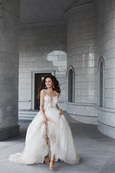 Счастливая модельная женщина со свадебной прической в белом кружевном платье бежит по двору древней церкви.