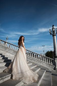 Красивая модель женщина с идеальным телом в роскошном свадебном платье стоит спиной на лестнице и позирует с голубым небом на фоне