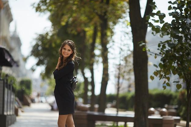 晴れた日に夏の街を歩いてスタイリッシュな黒のショートドレスで光沢のある笑顔で美しく、ファッショナブルなモデルの女の子