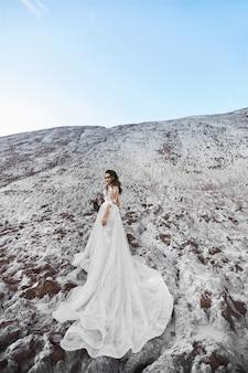 ブライダルブーケを維持し、日当たりの良い夏の日に屋外でポーズのウェディングドレスの若い女性。