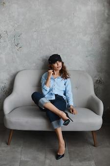 Модная девушка в туфлях на высоком каблуке, в шляпе, в синей рубашке и в джинсах. красивая молодая женщина в модном наряде сидит на диване и позирует в интерьере.