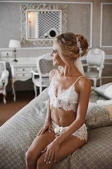 Счастливая длинноногая блондинка с идеальным телом и стильной свадебной прической в модном белом кружевном белье сидит на кровати и позирует в винтажном интерьере