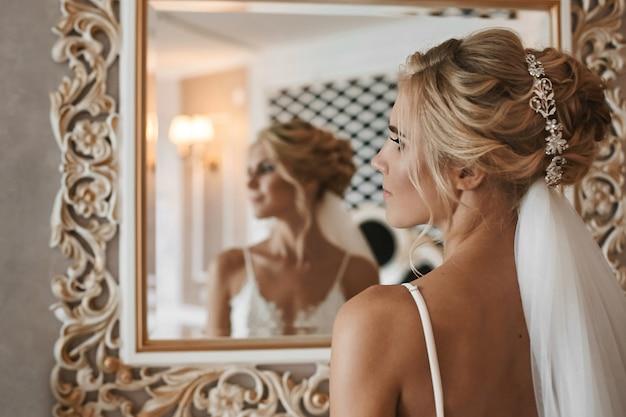Молодая женщина со стильной свадебной прической с украшениями, в модном белом кружевном белье позирует в винтажном интерьере