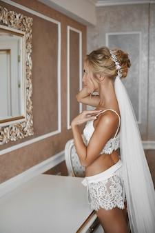 Молодая женщина со стройным телом и платиновыми светлыми волосами позирует возле зеркала в винтажном интерьере. блондинка модель девушка со стройным телом и свадебной прической в кружевном белье позирует в интерьере.